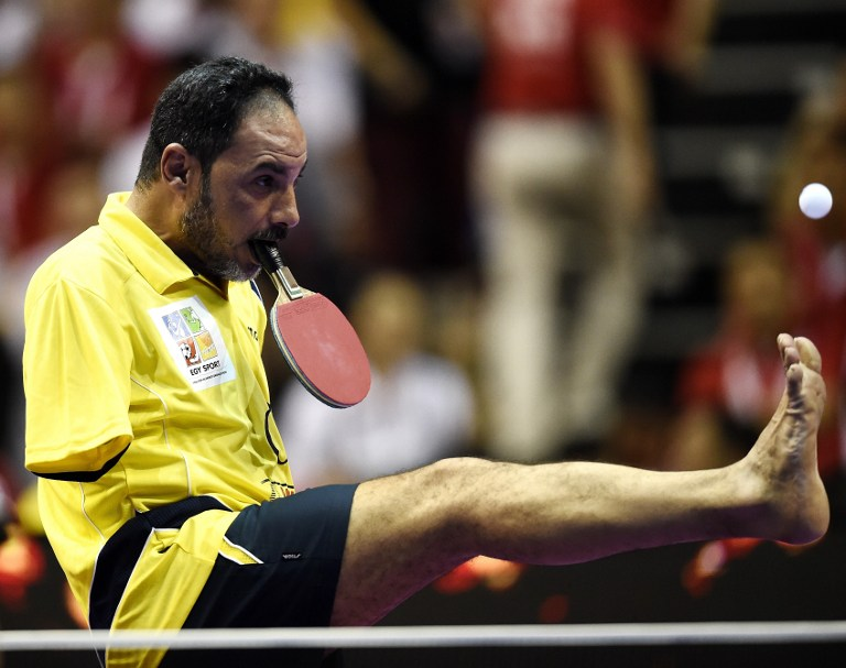 "Table Tennis player Ibrahim Hamato of Egypt serves with his foot during an exhibition match at the 2016 World Team Table Tennis Championships at Malawati Stadium in Shah Alam on March 6, 2016. / AFP / MANAN VATSYAYANA / ""The erroneous mention[s] appearing in the metadata of this photo by MANAN VATSYAYANA has been modified in AFP systems in the following manner: [Hamato] instead of [Hamadtou]. Please immediately remove the erroneous mention[s] from all your online services and delete it (them) from your servers. If you have been authorized by AFP to distribute it (them) to third parties, please ensure that the same actions are carried out by them. Failure to promptly comply with these instructions will entail liability on your part for any continued or post notification usage. Therefore we thank you very much for all your attention and prompt action. We are sorry for the inconvenience this notification may cause and remain at your disposal for any further information you may require."""
